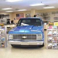 Chevy truck in retail store is surrounded by the two dozen truck parts catalogues LMC sends out for free.